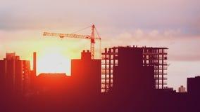 Dźwigowy działanie na budowy mieszkaniowej nieruchomości w mieście, konstruktory pracuje złotą godzinę zbiory