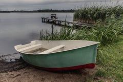 Dżdżysty wieczór przy Masuria jeziorem Rybaka ` s most w półdupkach i łódź obrazy royalty free