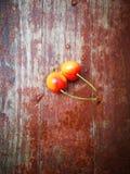 Dżdżystych wiśni owocowy lying on the beach na czerwonej drewnianej desce obrazy royalty free
