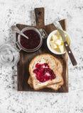 Dżem, masło, grzanka chleb na drewnianej tnącej desce na lekkim tle Obrazy Royalty Free