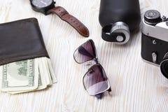 Dżentelmeński set: okulary przeciwsłoneczni, pachnidło, portfel, kamera, zegarek na drewnianym tle fotografia royalty free