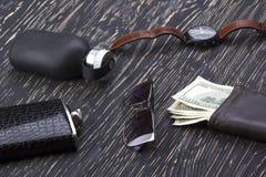 Dżentelmeński set: okulary przeciwsłoneczni, pachnidło, portfel, kolba, zegarek na drewnianym tle fotografia stock