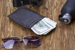 Dżentelmeński set: okulary przeciwsłoneczni, pachnidło, portfel, pieniądze, kamera na drewnianym tle zdjęcie royalty free