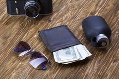 Dżentelmeński set: okulary przeciwsłoneczni, pachnidło, portfel, pieniądze, kamera na drewnianym tle fotografia stock