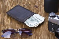 Dżentelmeński set: okulary przeciwsłoneczni, pachnidło, portfel, pieniądze, kamera na drewnianym tle obraz stock