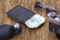 Dżentelmeński set: okulary przeciwsłoneczni, pachnidło, portfel, pieniądze, kamera na drewnianym tle zdjęcia stock