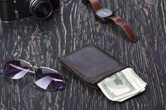 Dżentelmeński set: okulary przeciwsłoneczni, portfel, kamera, zegarek na drewnianym tle fotografia royalty free