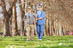Dżentelmen i męski pielęgniarki odprowadzenie w parku Obraz Royalty Free