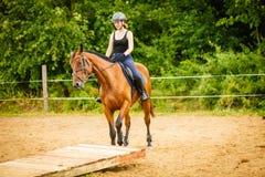 Dżokej dziewczyna robi końskiej jazdie na wsi łące Zdjęcie Royalty Free