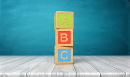 3d三个玩具块的翻译站立在一个塔的一张木书桌上的与在他们的信件A、B和C 图库摄影