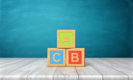 3d不同的颜色三个玩具块翻译与信件A、B和C的在站立在一张木书桌上的他们 图库摄影
