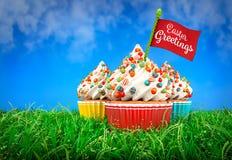 3D五颜六色的杯形蛋糕翻译在草的,复活节题材 库存例证