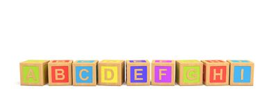 3d几块木玩具砖翻译与英国信件的在白色背景的字母顺序 免版税图库摄影