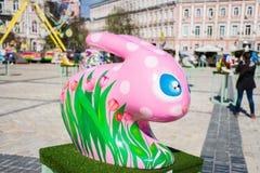 3D图春天在桃红色的复活节兔子与与被绘的郁金香的白色圆点在他的身体 美丽的复活节艺术装饰 免版税库存图片
