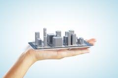 3D在智能手机和人手上的城市大厦 免版税库存图片