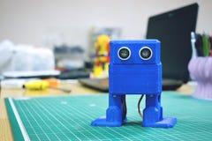 3D在设备和膝上型计算机背景打印了滑稽的跳舞的蓝色机器人  在自动三维3d打印的机器人模型 免版税库存照片
