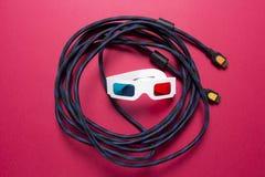 3d戏院概念通过HDMI缆绳 观看在3d电视的电影与HDMI 3d玻璃和hdmi在桃红色背景缚住 免版税库存图片