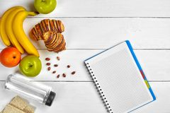 3d概念图象计划回报了 果子、新月形面包和笔记本在白色木背景 文本的空间 顶视图 库存照片