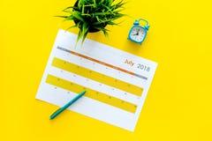 3d概念图象计划回报了 目标和任务为月 在闹钟附近的空白的月日历在黄色背景顶视图拷贝 免版税库存照片