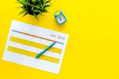 3d概念图象计划回报了 目标和任务为月 在闹钟附近的空白的月日历在黄色背景顶视图拷贝 库存照片