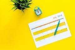 3d概念图象计划回报了 目标和任务为月 在闹钟附近的空白的月日历在黄色背景顶视图拷贝 免版税库存图片