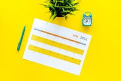 3d概念图象计划回报了 目标和任务为月 在闹钟附近的空白的月日历在黄色背景顶视图 免版税图库摄影