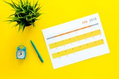 3d概念图象计划回报了 目标和任务为月 在闹钟附近的空白的月日历在黄色背景顶视图 库存照片