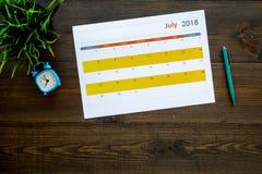 3d概念图象计划回报了 目标和任务为月 在闹钟附近的空白的月日历在黑暗的木背景顶视图 免版税库存图片