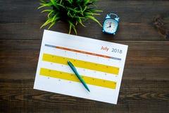 3d概念图象计划回报了 目标和任务为月 在闹钟附近的空白的月日历在黑暗的木背景顶视图 免版税库存照片