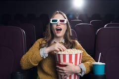 3d玻璃的年轻激动的妇女与玉米花观看的电影大篮子  库存图片