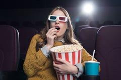 3d玻璃的激动的妇女吃玉米花和观看电影的 免版税库存照片