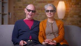 3d玻璃的资深白种人配偶在客厅观看在拥抱的电视的电影在沙发 影视素材