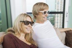 戴3D眼镜的愉快的夫妇,当在家时坐沙发 免版税库存图片