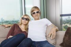 戴3D眼镜的轻松的夫妇,当在家时坐沙发 免版税库存照片