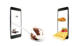 3D立体镜照片各种各样的甜点,在匙子的蛋糕,多士用莓,在智能手机的屏幕之外,被隔绝 库存照片