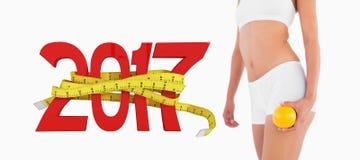 3D苗条女性身体的综合图象与拿着桔子的白色运动服的 免版税库存照片