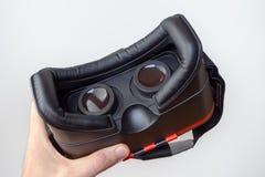 3D虚拟现实耳机在一只手上有白色背景 免版税图库摄影