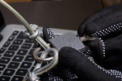 3d计算机例证监控程序证券 通入的保护对数据的 膝上型计算机受安全缆绳和锁的保护 与手套t的一个攻击者 库存图片