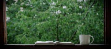 D'été toujours la vie confortable : tasse de café chaud et de livre ouvert sur le rebord de fenêtre et la pluie de vintage dehors photographie stock