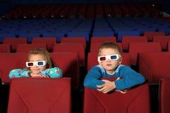 3D玻璃的两个小孩子观看电影的 免版税库存照片