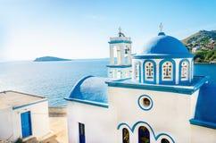 白色教会典型的希腊蓝色圆顶有在晴朗的d的海视图 免版税库存照片