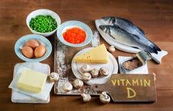 维生素D的食物来源在木背景的 图库摄影
