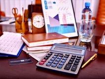 D'affaires toujours la vie avec la calculatrice sur la table dedans Image stock