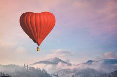D air balloon in the shape of a heart flying in morning mountains Royalty Free Stock Photos