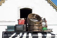 D'annata le attrezzature elettroniche caricate vecchia automobile dipinte in bianco e nero di vecchio caso resta sulle erbe verdi Immagini Stock Libere da Diritti
