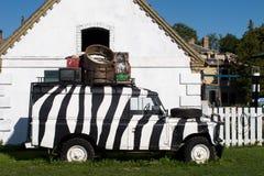 D'annata le attrezzature elettroniche caricate vecchia automobile dipinte in bianco e nero di vecchio caso resta sulle erbe verdi Immagine Stock Libera da Diritti