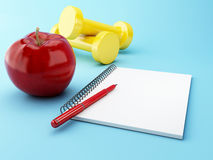3D Apple with a notepad and dumbbell. Royalty Free Stock Photo