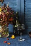 D'automne d'humeur toujours la vie avec un bouquet des feuilles d'automne et d'un verre de vin rouge Photo stock