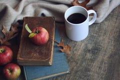 D'automne toujours la vie avec les pommes, la couverture chaude, les livres et les feuilles au-dessus du fond en bois rustique Photographie stock
