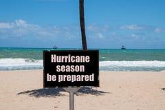 D'avertissement connectez-vous la plage à côté du tronc d'un palmier un jour ensoleillé avec un avertissement clair bleu de ciel  photographie stock